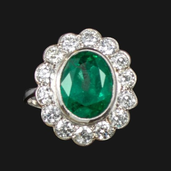 An emerald and diamond cluster ring, centred with an oval-shaped...