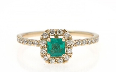 An emerald and diamond ring set with an emerald-cut emerald encircled by numerous diamonds, mounted in 14k gold. Size 59.
