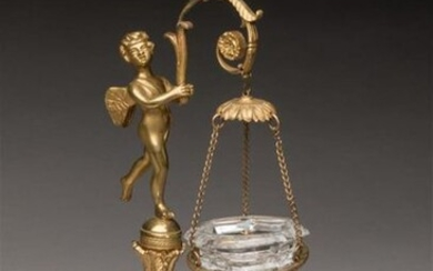 Gilded bronze VEILLEUSE decorated with a cherub standing on a torch, holding in his hands a leafy branch, carrying the crystal tank. Circular base with ice bottom, resting on three runners. Empire period. H. 28, D. 13 cm.