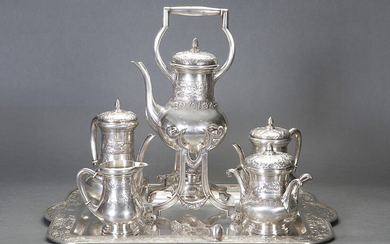 Large tea and coffee set in 916 Spanish silver, c.1920. Relief decoration of vine leaves and grapes. Set composed by: big rectangular tray with handles, samovar, teapot, coffee pot, milk pot, sugar bowl. Associated tweezers. Engraved initials. Weight: 7