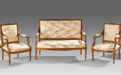 Louis XVI style gilded wood lounge furniture including 4 armchairs and a sofa. Sculpted decoration of ribbon knots, friezes of knotted ribbons and acanthus leaves. Beautiful embroidered fabric upholstery with flower decoration.