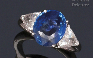 White gold ring set with an oval facetted sapphire set with troika diamonds. Total weight of the diamants : about 0.70 carat. Weight of saphir : 4.07 carats. Origine : Sri Lanka. It is accompanied by a certificate from the GIA (American gemmological...