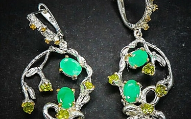 a pair of emerald and peridot ear pendants each set with numerous oval and circular-cut emeralds and peridots, mounted in rhodium plated sterling silver.
