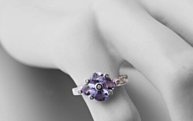 750 thousandths white gold ring set with four oval-shaped tanzanites interspersed and shouldered with modern-cut diamonds.