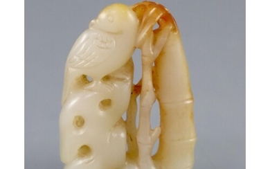 A Chinese pale celadon and russet jade carving of a bird on ...