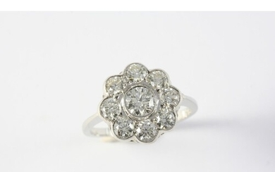 A DIAMOND CLUSTER RING of flowerhead form, set with nine cir...