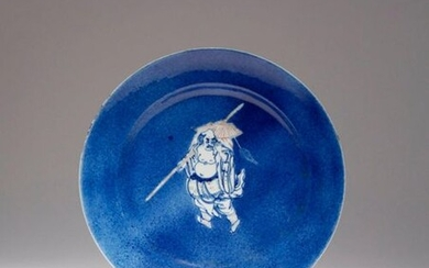 A RARE CHINESE UNDERGLAZE BLUE AND RED POWDER BLUE-GROUND DISH KANGXI 1662-1722 Painted to the centre with a travelling monk carrying a large bundle and a fly whisk over his shoulder on a pole, the figure reserved on a mottled powder blue ground, with...