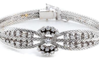 A VINTAGE 18CT WHITE GOLD DIAMOND BRACELET; centring a round brilliant cut diamond of approx. 0.13ct to part double surround of 16 b...