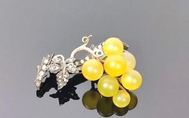 Brooch in yellow and white gold simulating a vine branch holding a bunch of grapes in tinted glass. The vine is decorated with small diamonds.