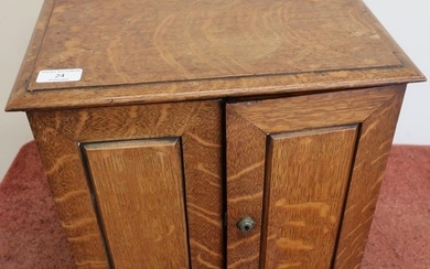 Edwardian oak table/smokers cabinet enclosed by two panelled...