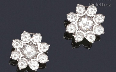"""Pair of earrings """" Fleurs """" in white gold, set with brilliant-cut diamonds, the one in the more important center. Clasp with stem and safety clasp. Total weight of the diamants : about 4.6 carats. P. Brut : 9,6 g."""