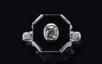 RING in 750 thousandths white gold, decorated with an old cut diamond on a background of onyx surrounded by six brilliant-cut diamonds. The shoulder of the kitten in fleur-de-lys. Finger size: 54. Gross weight: 5.3 g. Approximate weight of the central...