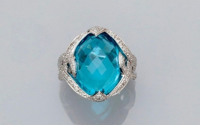White gold ring, 750 MM, set with a briolette-cut oval blue topaz weighing approximately 18 carats in two diamond ribbons, 18 x 13 mm, size: 55, weight: 12.6gr. rough.