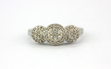 A 10ct white gold (stamped 10k) diamond set triple cluster ring, (J).