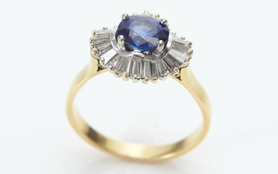 A SAPPHIRE AND DIAMOND RING IN TWO TONE 18CT GOLD, THE OVAL CUT BLUE SAPPHIRE ESTIMATED 1.67CTS, WITHIN A SURROUND OF TAPERED BAGUET...