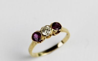 A ruby and diamond three-stone ring, comprising a central br...