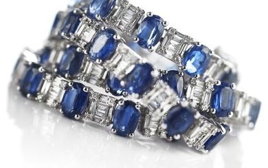 A sapphire and diamond bracelet set with numerous oval-cut sapphires and numerous brilliant and baguette-cut diamonds, mounted in 18k white gold.