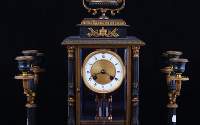 Empire mantel clock with paired candlesticks. Late XIX century.