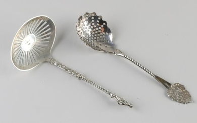 Two silver scattering spoons, 833/000, a scattering