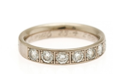A diamond eternity ring set with seven brilliant-cut diamonds, mounted in 14k white gold. Size 50.