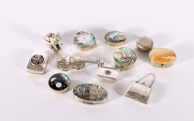 A group of twelve silver and white metal pill boxes includin...