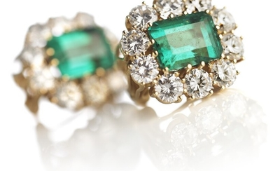 A pair of emerald and diamond ear pendants each set with an emerald-cut emerald encircled by numerous brilliant-cut diamonds, mounted in 18k gold. G-H/VS. (2)