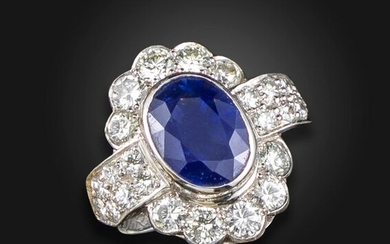 A sapphire and diamond cluster ring by Geoffrey Rowlandson, centred with an oval-shaped sapphire weighing approximately 4.50cts, set within a surround of round brilliant-cut diamonds, with further diamonds to the shoulders in white gold, signed...