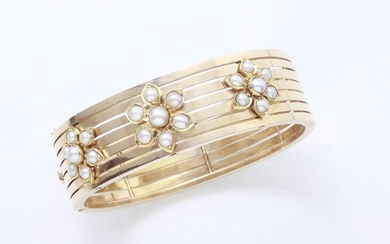 Bracelet opening rush openwork gold 750 thousandths applied with 3 flowers punctuated with half pearls. It is embellished with a ratchet clasp with safety chain. Work of the second half of the 19th century.