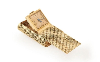 VAN CLEEF & ARPELS, circa 1950. Hooded bag watch, called Captive, in 18K (750/°°) yellow gold with wickerwork decoration, gold dial, blued steel hand. Mechanical Jaeger Lecoultre movement. Signed and numbered, the watch is held in place by a vest chain.
