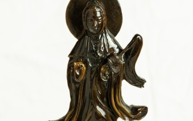 A Chinese Tiger Eye carving of the Goddess of Mercy with aura on a carved wooden stand, total height 20cm