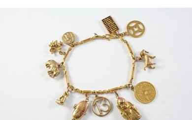 A GOLD CHARM BRACELET suspending assorted gold charms, total...