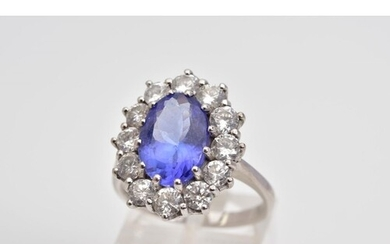 A MODERN LARGE TANZANITE AND DIAMOND OVAL CLUSTER RING, an o...