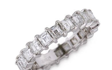 A diamond and eighteen karat white gold eternity band...