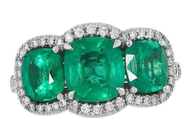 AN EMERALD AND DIAMOND RING set with three cushion cut