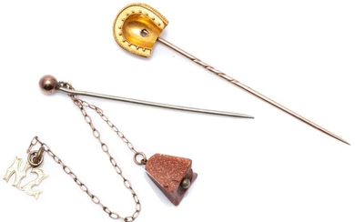 TWO ANTIQUE STICK PINS; one with 14ct gold horseshoe (missing stone) on gilt metal pin, other carved goldstone bell (chipped) and NZ...