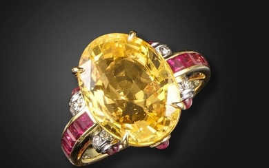 A yellow sapphire, ruby and diamond ring, the oval-shaped sapphire weighs 11.64cts, claw-set with round brilliant-cut diamonds, cabochon and calibré-cut rubies to the scroll shoulders in platinum and gold, size O